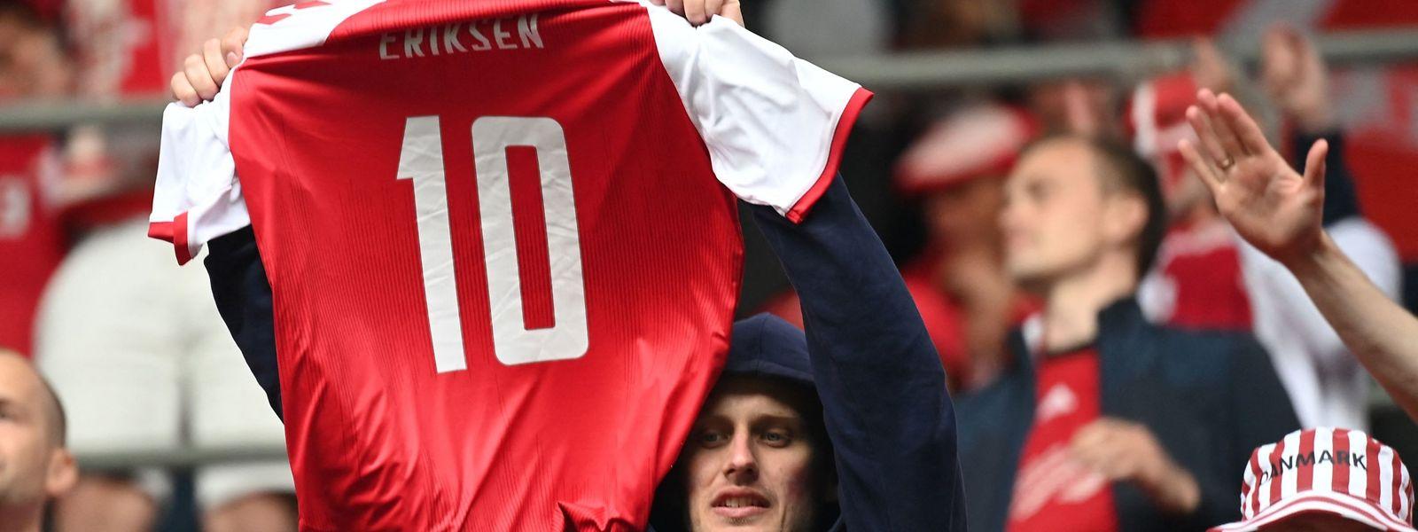 Ein Fan hält ein Trikot von Christian Eriksen in die Höhe.