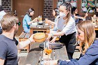 24.05.2021, Berlin: Thuy Nhi Nguyen (M), Kellnerin, bedient im Berliner Bezirk Prenzlauer Berg in einem Restaurant für asiatische Fusionsküche Gäste. Foto: Christoph Soeder/dpa +++ dpa-Bildfunk +++