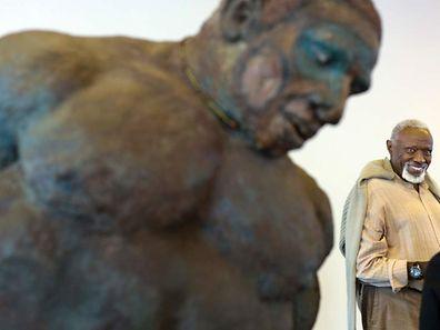 Photo du 15 juin 2013 montrant Ousmane Sow souriant derrière l'une de ses sculptures lors du vernissage de son exposition à la citadelle de Besançon (France).