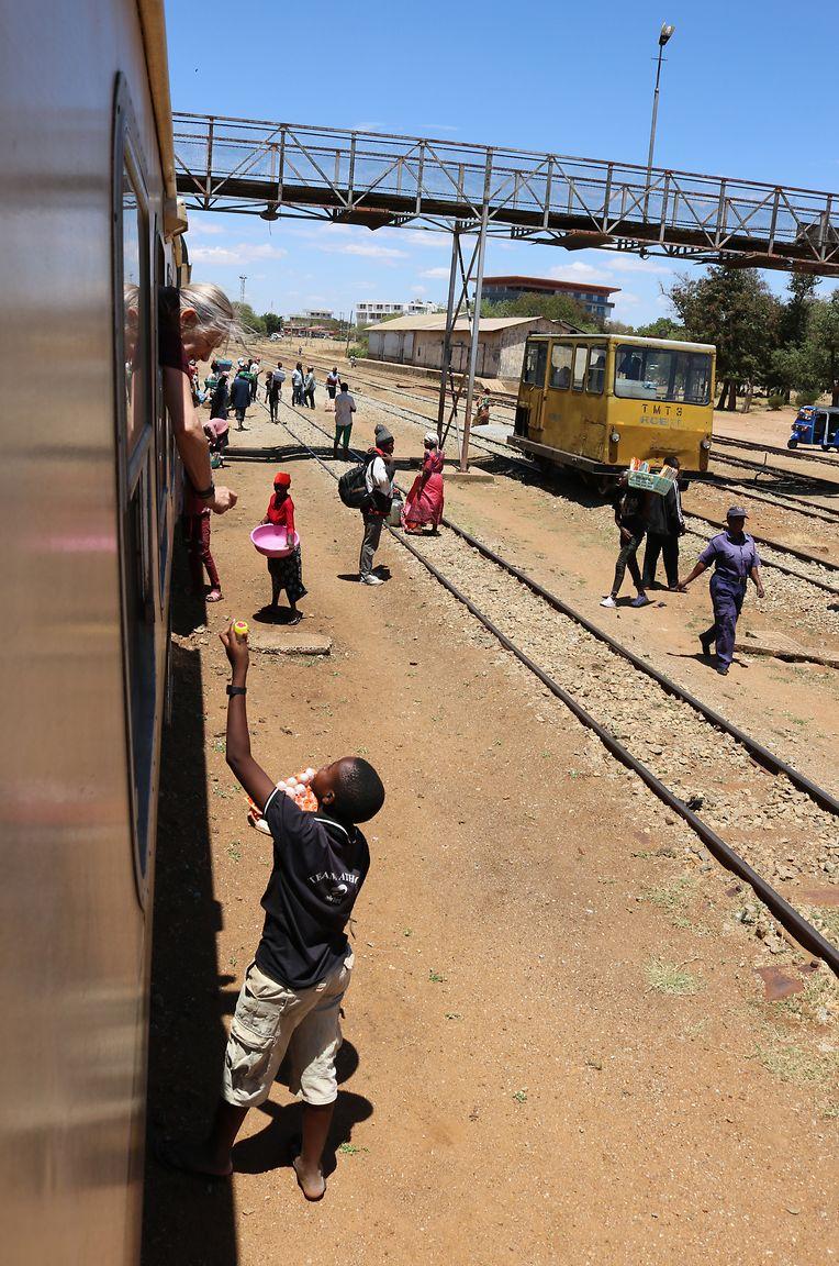 Verkaufsgespräch am Zugfenster: An Tansanias Bahnhöfen bieten Verkäufer immer wieder etwas an.