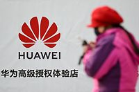 A woman uses her smartphone while walking past advertising outside a Huawei store in Beijing on January 29, 2019. - Asian markets fell on January 29 as the charging of Chinese giant Huawei in the US cast a shadow over upcoming trade talks, while investors were also tracking a Wall Street sell-off fuelled by concerns corporate profits. (Photo by WANG ZHAO / AFP)