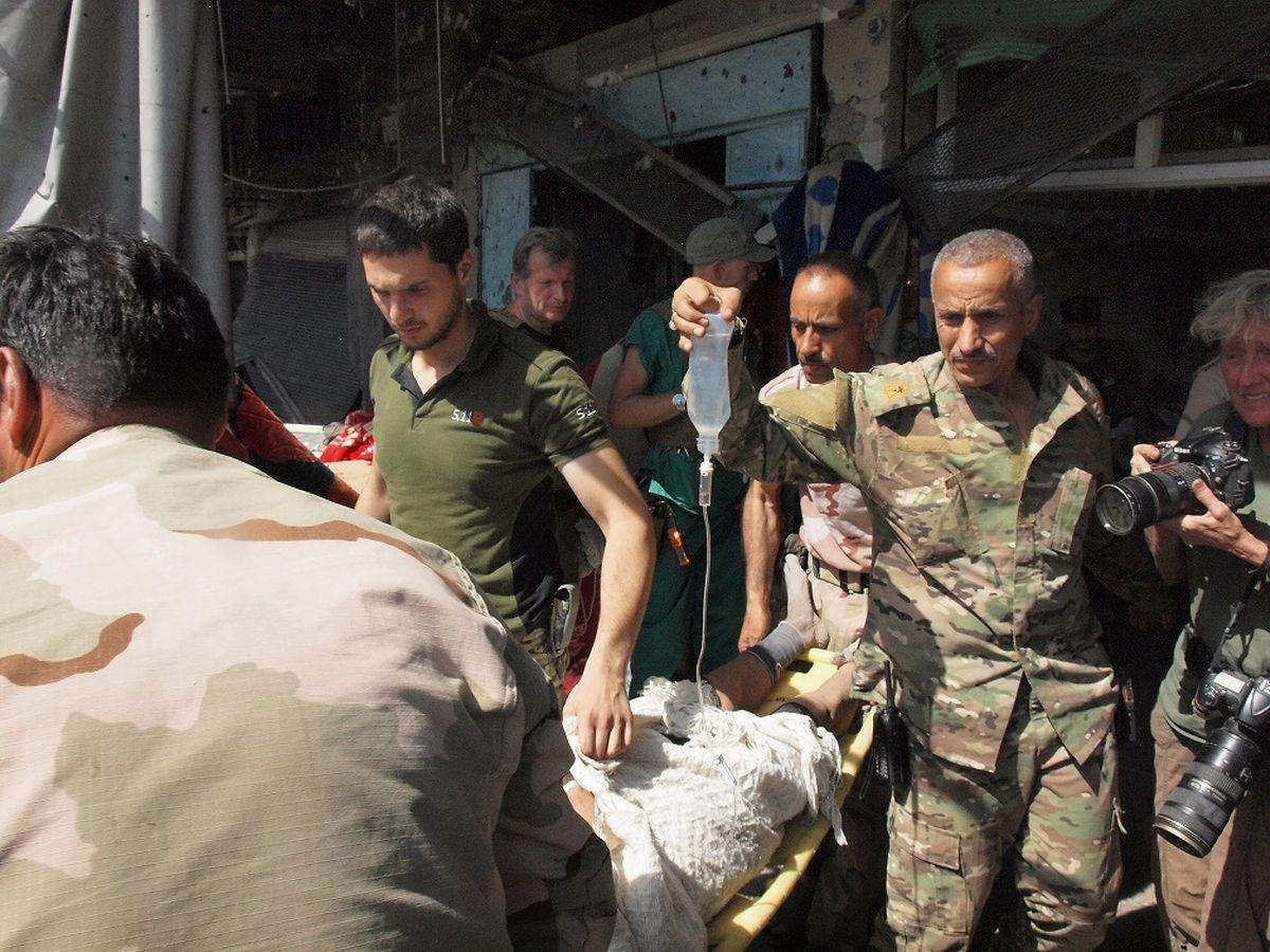 Irakische Soldaten tragen einen jungen Mann in das Feldlazarett.