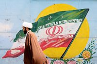 """An Iranian cleric walks past a mural painting of the national flag on August 27, 2019. - Iranian President Hassan Rouhani today told the United States to """"take the first step"""" by lifting all sanctions against Iran, dampening down the likelihood of meeting US counterpart Donald Trump. (Photo by ATTA KENARE / AFP)"""