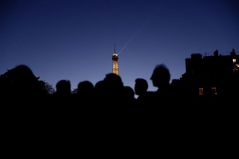 Wartende stehen an, um von Jacques Chirac Abschied zu nehmen. Im Hintergrund leuchtet der Eiffelturm.