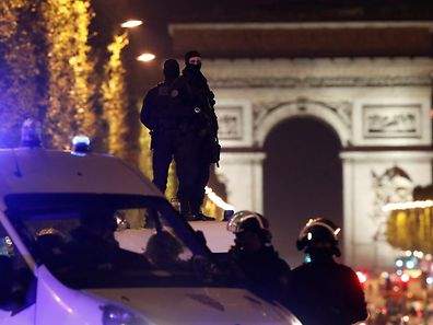 Masked police stand on top of their vehicle on the Champs Elysees Avenue