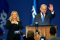 "Israeli Prime Minister Benjamin Netanyahu and his wife Sara address supporters at the Likud party campaign headquarters in the coastal city of Tel Aviv early on March 3, 2020, after polls officially closed. - Netanyahu claimed ""a giant victory"" in elections on March 3, boasting that his right-wing Likud party had defied ""all expectations"" in the country's third vote in less than a year. After exit polls by three networks forecast that Likud and its allies were on track to win 59 parliamentary seats -- two short of majority -- the premier mocked those who ""predicted the end of Netanyahu"". (Photo by GIL COHEN-MAGEN / AFP)"