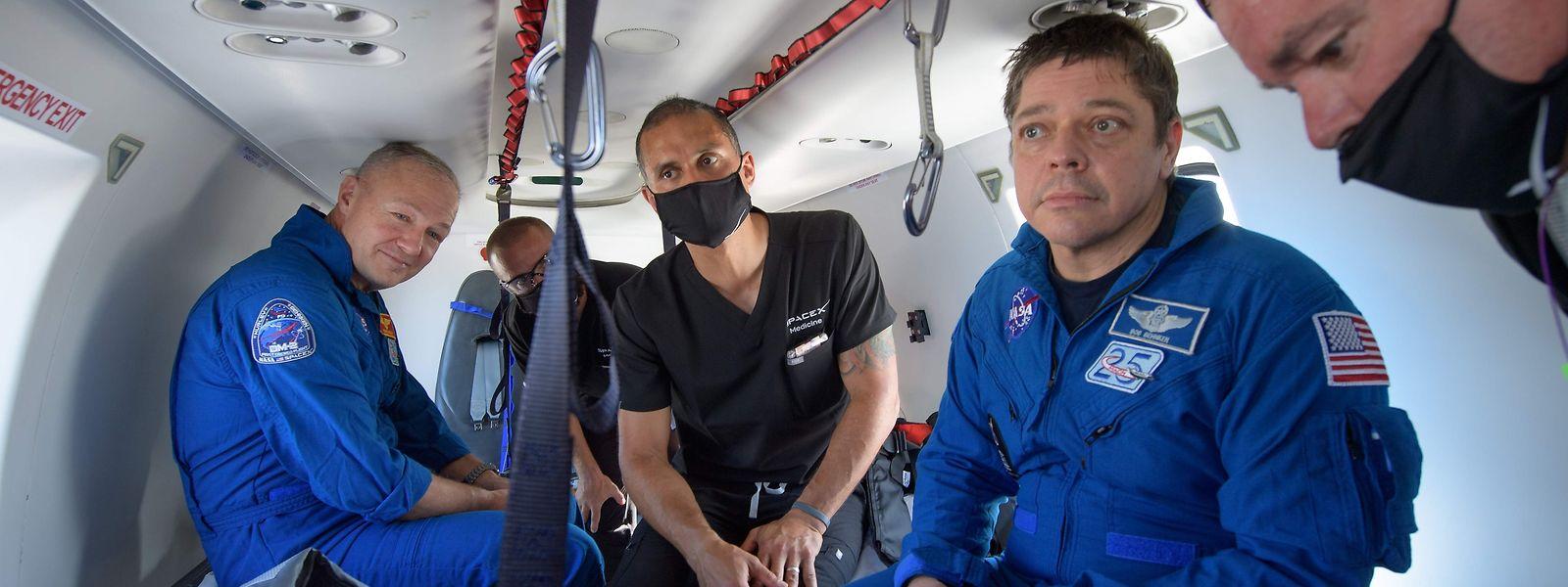 Die beiden Astronauten Bob Behnken (r.) und Doug Hurley nach der Landung im Golf von Mexiko in einem Hubschrauber.