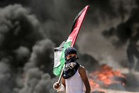 A Palestinian boy holding his national flag looks at clashes with Israeli security forces near the border between the Gaza Strip and Israel east of Gaza City on May 14, 2018, as Palestinians protest over the inauguration of the US embassy following its controversial move to Jerusalem. Dozens of Palestinians were killed by Israeli fire on May 14 as tens of thousands protested and clashes erupted along the Gaza border against the US transfer of its embassy to Jerusalem, after months of global outcry, Palestinian anger and exuberant praise from Israelis over President Donald Trump's decision tossing aside decades of precedent. / AFP PHOTO / MAHMUD HAMS