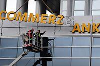 """ARCHIV - 07.11.2013, Hessen, Frankfurt/Main: Arbeiter demontieren den Schriftzug an einer Commerzbankfiliale. Nach der geplatzten Fusion mit der Deutschen Bank stemmt sich die Commerzbank mit einem radikalen Konzernumbau gegen die Niedrigzinsen und den scharfen Wettbewerb. (Zu dpa """"Commerzbank baut radikal um - Kunden drohen höhere Gebühren"""") Foto: Daniel Reinhardt/dpa +++ dpa-Bildfunk +++"""