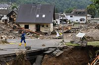 TOPSHOT - A man walk on a partially slipped road amid destroyed houses after the floods caused major damage in Schuld near Bad Neuenahr-Ahrweiler, western Germany, on July 16, 2021. - Devastating floods have torn through entire villages and killed at least 129 people in Europe, most of them in western Germany where stunned emergency services were still combing the wreckage on July 16, 2021. (Photo by CHRISTOF STACHE / AFP)