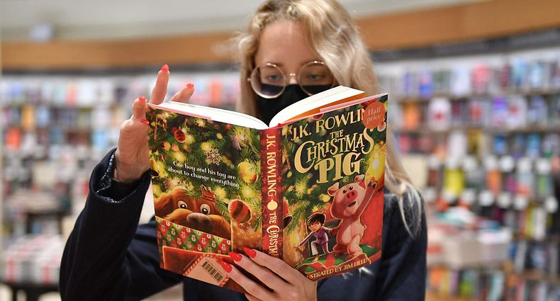 """A member of staff holds a copy of JK Rowling's new children's novel """"The Christmas Pig"""" at the Waterstones Piccadilly bookshop in London on October 12, 2021. (Photo by JUSTIN TALLIS / AFP)"""