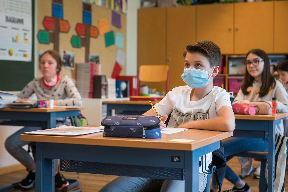 Die Schüler sitzen an einzelnen Bänken. Manche haben ihre Maske während dem Unterricht anbehalten.