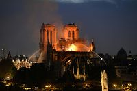 TOPSHOT - Firefighters douse flames rising from the roof at Notre-Dame Cathedral in Paris on April 15, 2019. - A major fire broke out at the landmark Notre-Dame Cathedral in central Paris sending flames and huge clouds of grey smoke billowing into the sky, the fire service said. The flames and smoke plumed from the spire and roof of the gothic cathedral, visited by millions of people a year, where renovations are currently underway. (Photo by Bertrand GUAY / AFP)