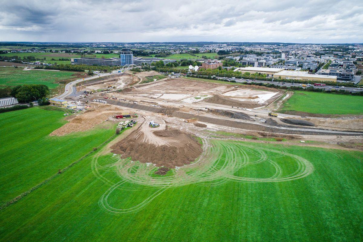 """Hier das Gelände, auf dem das Stadion gebaut wird. Neben der Straße links entsteht das Stadion. Rechts daneben ein Parkplatz mit Stellplätzen für Offizielle. Und daneben, wo momentan noch Grünfläche ist, kommt das Gebäude für den """"Service des sports""""."""
