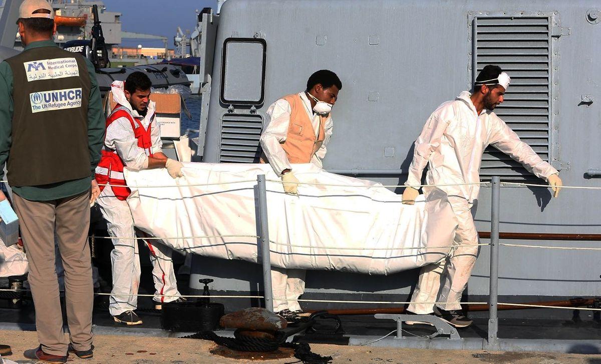 Der Körper eines gestorbenen Migranten wird an Land getragen.