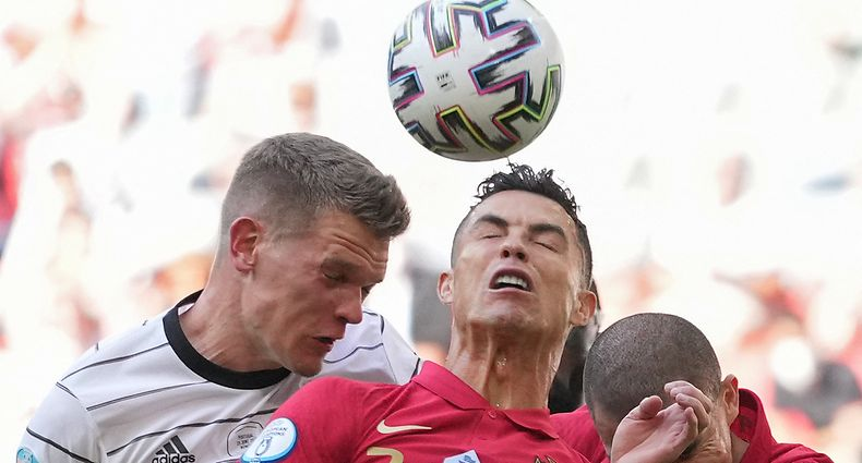 TOPSHOT - Portugal's forward Cristiano Ronaldo (R) goes up for a header against Germany's defender Matthias Ginter (L) during the UEFA EURO 2020 Group F football match between Portugal and Germany at Allianz Arena in Munich on June 19, 2021. (Photo by Matthias Schrader / POOL / AFP)