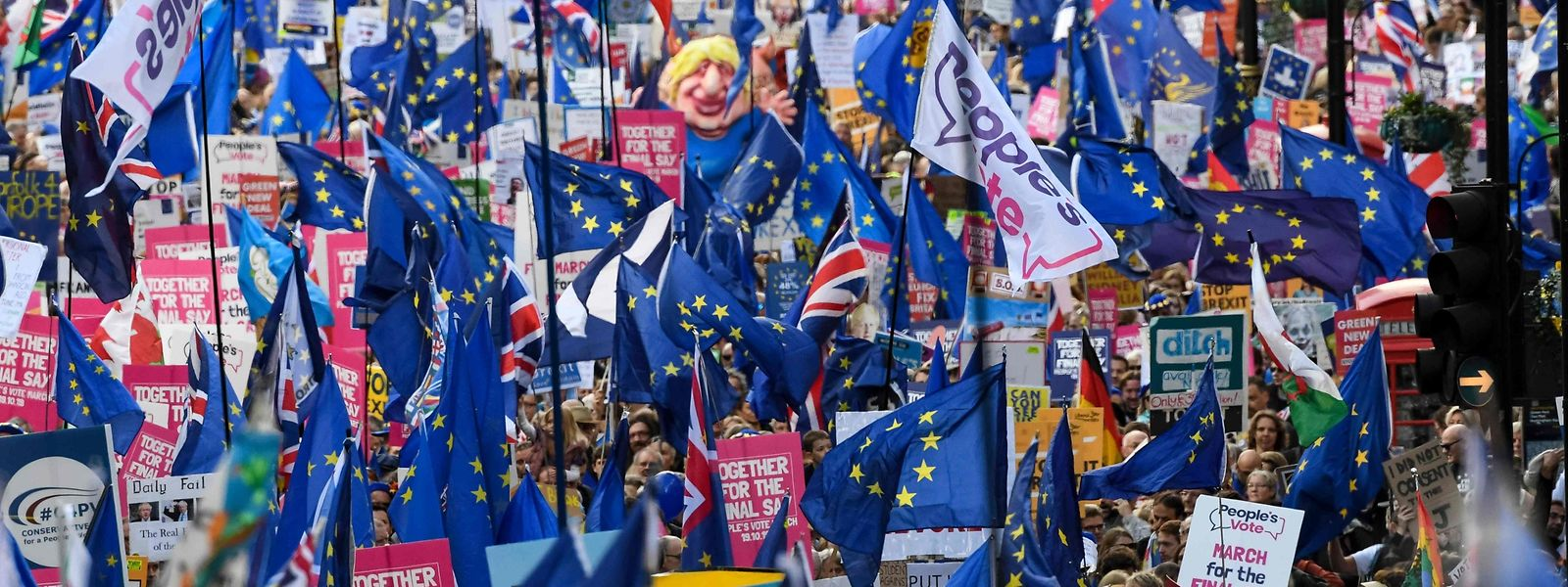 """TOPSHOT - Demonstrators hold placards and EU and Union flags as they take part in a march by the People's Vote organisation in central London on October 19, 2019, calling for a final say in a second referendum on Brexit. - Thousands of people march to parliament calling for a """"People's Vote"""", with an option to reverse Brexit as MPs hold a debate on Prime Minister Boris Johnson's Brexit deal. (Photo by Niklas HALLE'N / AFP)"""