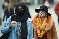 Women wear face masks or coverings due to the COVID-19 pandemic, as they walk in Liverpool, north west England on October 2, 2020, following the announcement of new local restrictions for certain areas in the northwest of the country, due to a resurgence of novel coronavirus cases. - The British government on Thursday extended lockdowns to Liverpool and several other towns in northern England, effectively putting more than a quarter of the country under tighter coronavirus restrictions. Health Secretary Matt Hancock said limits on social gatherings would be extended to the Liverpool City region, which has a population of about 1.5 million. (Photo by Oli SCARFF / AFP)