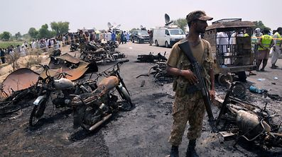 A soldier stands guard amid burnt out cars and motorcycles at the scene of an oil tanker explosion in Bahawalpur, Pakistan June 25, 2017