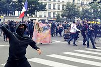 Demonstrators clash with police at the end of a demonstration part of a national day of protest against French legislation making a Covid-19 health pass compulsory to visit a cafe, board a plane or travel on an inter-city train, in Paris on July 31, 2021. - The legislation passed by parliament the week before has sparked mass protests in France but the government is determined to press ahead and make the health pass a key part of the fight against Covid-19. A valid health pass is generated by two jabs from a recognised vaccine, a negative coronavirus test or a recent recovery from infection. The legislation also makes vaccination compulsory for health-workers and carers. The pass has already been obligatory from July 21 for visits to museums, cinemas and cultural venues with a capacity of more than 50 people. (Photo by Alain JOCARD / AFP)