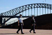 Polizisten mit Gesichtsmasken patrouillieren vor der Harbour Bridge in Sydney.Der Lockdown in der australischen Metropole Sydney wird wegen der Ausbreitung der hochansteckenden Delta-Variante bis mindestens zum 30. Juli verlängert.