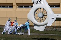 Medical staff transport a patient on a stretcher to a medical helicopter at the Emile Muller Hospital in Mulhouse, eastern France, on March 22, 2020, on the seventh day of a lockdown aimed at curbing the spread of the COVID-19 (novel coronavirus) in France. (Photo by PATRICK HERTZOG / AFP)