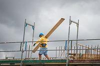 ARCHIV - 08.07.2019, Niedersachsen, Hannover: Ein Bauarbeiter trägt auf einer Baustelle auf einem Hausdach ein Brett. Die Corona-Krise hat die deutsche Wirtschaft Ökonomen zufolge im ersten Quartal ausgebremst. Ausgangsbeschränkungen, geschlossene Grenzen und Geschäfte brachten das Wirtschaftsleben seit Mitte März in Teilen zum Erliegen. Foto: Christophe Gateau/dpa +++ dpa-Bildfunk +++
