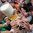 People get the first beer mugs after the official opening of the 184th Oktoberfest, Munich's annual beer festival, on September 16, 2017 in Munich, southern Germany. The world's largest beer festival is held from September 16 until October 3, 2017.  / AFP PHOTO / dpa / Sven Hoppe / Germany OUT