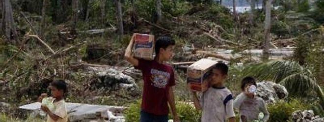 Überlebende tragen Gegenstände und Lebensmittel in dem vom Tsunami zerstörten Dorf Pororogat, auf den Mentawai Inslen westlich vom indonesischen Sumatra.