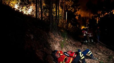 TOPSHOT - Firefighters rest during a wildfire at Penela, Coimbra, central Portugal, on June 18, 2017.  A wildfire in central Portugal killed at least 25 people and injured 16 others, most of them burning to death in their cars, the government said on June 18, 2017. Several hundred firefighters and 160 vehicles were dispatched late on June 17 to tackle the blaze, which broke out in the afternoon in the municipality of Pedrogao Grande before spreading fast across several fronts.  / AFP PHOTO / PATRICIA DE MELO MOREIRA
