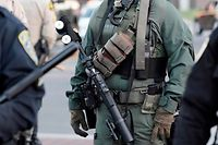 """A 40mm tactical launcher and """"less lethal"""" ammunition is carried by a police officer during a Black Lives Matter protest against racial injustice and police brutality in La Mesa, California, on August 1, 2020. (Photo by Bing GUAN / AFP)"""