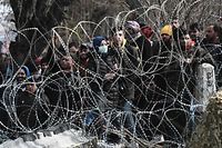 TOPSHOT - This picture taken from the Greek side of the Greece-Turkey border near Kastanies, shows migrants waiting on the Turkish side on March 2, 2020. - Greece was on a state of alert on March 1, 2020 as it faced an influx of thousands of migrants seeking to cross the border from Turkey, with locals fearing a new immigration crisis. More than 13,000 migrants have gathered on the Turkish side of the river which runs 200 kilometres (125 miles) along the frontier and separates them from Greece and therefore the European Union. The flow of migrants from Turkey has triggered EU fears of a re-run of the 2015 migrant emergency when Greece became the main EU entry point for a million migrants, most of them refugees fleeing the Syrian civil war. (Photo by Sakis MITROLIDIS / AFP)