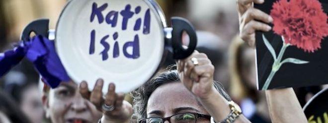 """Une femme lors d'une manifestation à Istanbul. On peut lire """"EI tueurs"""""""
