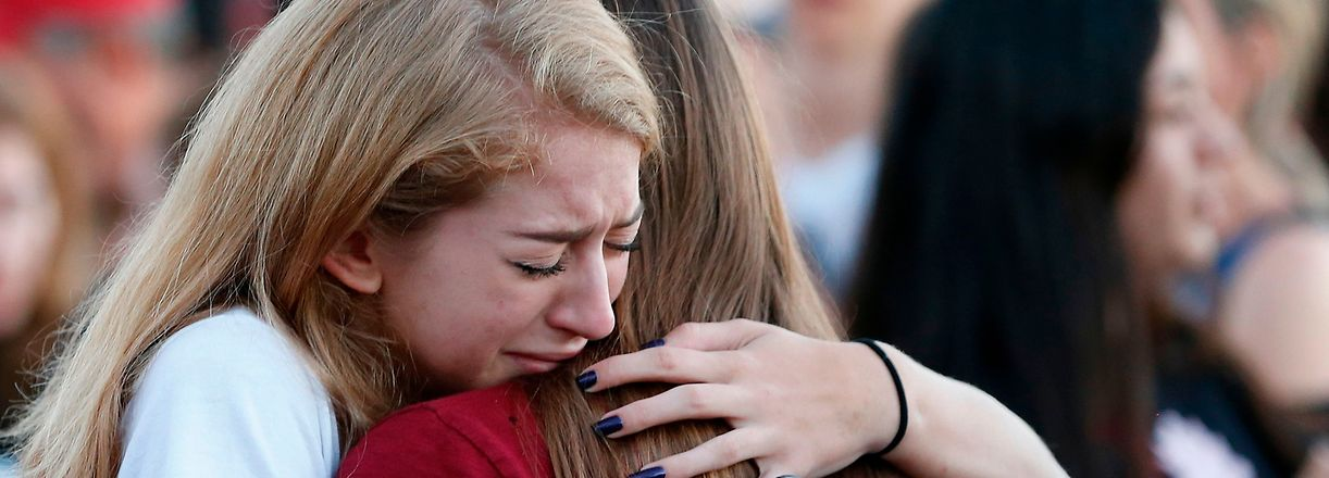 (FILES) In this file photo taken on February 15, 2018 Mourners grieve as they await the start of  a candlelight vigil for victims of the Marjory Stoneman Douglas High School shooting in Parkland, Florida.  There have been renewed calls for stricter gun control in the United States following the shooting deaths last week of 14 students and three adults at a Florida high school. The White House has said following the Florida school shooting that President Donald Trump supports efforts to improve the federal background check system for gun buyers. / AFP PHOTO / RHONA WISE