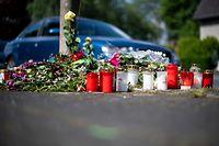 29.04.2019, Nordrhein-Westfalen, Moers: Blumen und Kerzen stehen an der Stelle, an der eine unbeteiligte Frau bei einem mutmaßlichen Autorennen verletzt und später gestorben ist. Zwei Raser sollen sich in PS-starken Autos auf der zweispurigen Straße ein illegales Autorennen geliefert haben. Dabei kollidierte ein Fahrer mit dem Kleinwagen des 43-jährigen Todesopfers. Foto: Marius Becker/dpa +++ dpa-Bildfunk +++