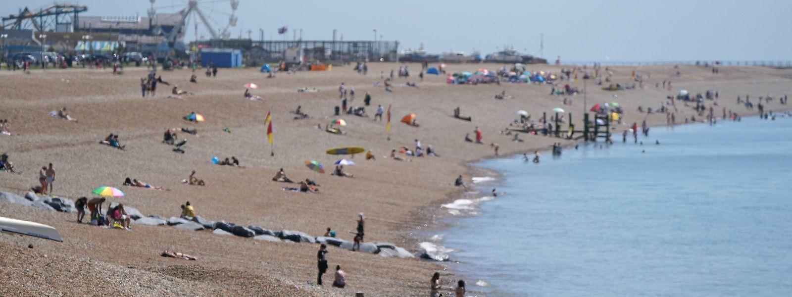 """Einige Menschen genießen am Strand von Hastings die Sonne und das warme Wetter. Der """"Tag der Freitheit"""" könnte um vier Wochen nach hinten verlegt werden."""