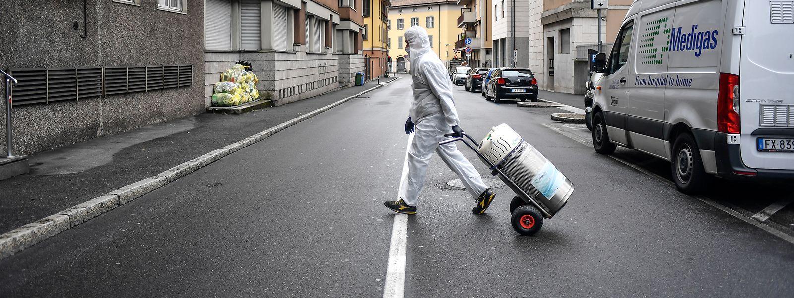 Bergamo: Ein Arbeiter imSchutzanzug liefert eineSauerstoffflasche.