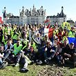 """Protestors wearing a """"Yellow Vest"""" (Gilet Jaune) sit and wave French flags in front of Chambord Castle's (Chateau de Chambord) on February 23, 2019 as he came to show his support to """"Yellow Vests"""" (Gilets Jaunes) during a picnic as part of an anti-government demonstration. - 'Yellow vest' protesters take to the streets for 15th consecutive Saturday. (Photo by JEAN-FRANCOIS MONIER / AFP)"""