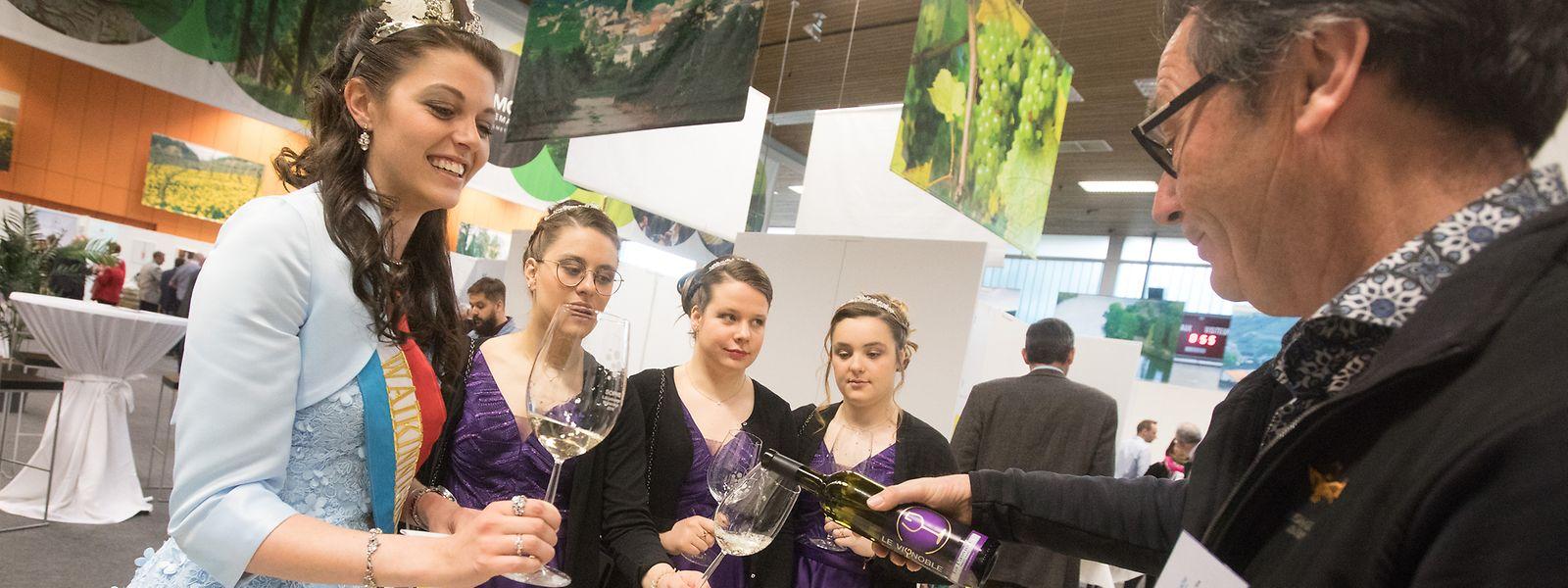 Der Weinkönigin Sophie und ihren Prinzessinnen wird weißer Wein eingeschenkt.