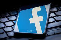 ARCHIV - 25.03.2018, Großbritannien, ---: ILLUSTRATION - Das Facebook-Logo wird auf einem Smartphone gespiegelt, das auf einer Tastatur liegt. Facebook hat Mitarbeiter ausgewählte Aufnahmen von Nutzern aus seinem Chatdienst Messenger anhören und abtippen lassen. Foto: Dominic Lipinski/PA Wire/dpa +++ dpa-Bildfunk +++