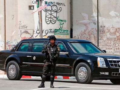 An armoured limousine part of the convoy of the US president drives past Israel's controversial separation barrier in the West Bank city of Bethlehem on May 23, 2017, following a meeting between Donald Trump and the Palestinian leader Mahmud Abbas. Trump's visit to Israel and the Palestinian territories is part of his first trip abroad as president, and follows an initial leg in Saudi Arabia, where he urged Islamic leaders to confront extremism. / AFP PHOTO / HAZEM BADER