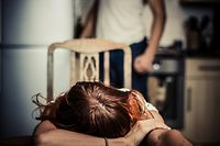 Young woman is reesting her head on a kitchen table, her abusive partner hovering in the background