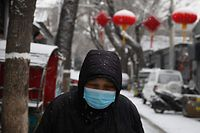 A woman wears a protective face mask as she walks in an alley in Beijing on February 5, 2020. - China's struggle to contain the deadly coronavirus is deepening concerns about the impact on the world's number-two economy, as factories stay closed and millions of consumers remain holed up at home. (Photo by GREG BAKER / AFP)