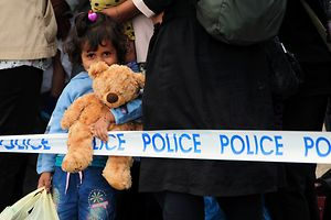 Migrant girl with a teddy bear waits with other migrants for their transport at the police collection point close to the Hungarian-Serbian border near Roszke village on September 6, 2015. Europe is deeply divided over how to handle the continent's biggest refugee crisis since the end of World War II. AFP PHOTO / CSABA SEGESVARI