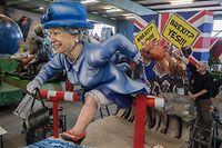 26.02.2019, Rheinland-Pfalz, Mainz: Mit einem Asylantrag in der Hand springt die Queen bei der Präsentation der Motivwagen des Mainzer Carneval-Vereins (MCV) angesichts des drohenden Brexits über den Schlagbaum in die EU. Die Wagen werden bei Rosenmontagszug durch die Mainzer Innenstadt rollen. Foto: Boris Roessler/dpa +++ dpa-Bildfunk +++