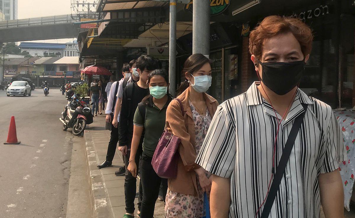 Menschen tragen im Stadtviertel Thonglor Masken zum Schutz vor Smog.