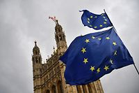 EU flags held by demonstrators flutter as the Union flag flies atop the Houses of Parliament in central London on April 4, 2019. in central London on April 4, 2019. - Britain's government redoubled its efforts Thursday to win over the main opposition party in a last-gasp bid to avoid a chaotic exit from the European Union next week. (Photo by Daniel LEAL-OLIVAS / AFP)