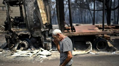 A man passes by his truck burnt during yesterday's wildfire in Figueiro dos Vinhos on June 18, 2017. A wildfire in central Portugal killed at least 57 people and injured 59 others, most of them burning to death in their cars, the government said on June 18, 2017. Several hundred firefighters and 160 vehicles were dispatched late on June 17 to tackle the blaze, which broke out in the afternoon in the municipality of Pedrogao Grande before spreading fast across several fronts.    / AFP PHOTO / PATRICIA DE MELO MOREIRA