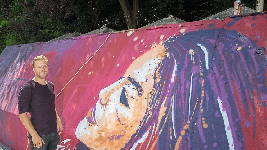 """Kunstsprayer Raphaël Gindt in Aktion in Herserange: Das Frauenporträt auf der Stützmauer ist eine Auftragsarbeit im Rahmen des Festivals """"Kufa's Urban Art""""."""