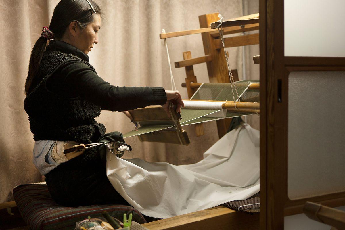 Dann werden die gefärbten Garne wieder von den Fadenverknüpfungen befreit, mit Leim verstärkt und der Musterung entsprechend im Webstuhl sortiert und befestigt. Die historischen Jibata-Webstühle, die über einen am Weber befestigten Rückengurt gespannt werden, funktionieren übrigens noch genau so wie vor 1500 Jahren.